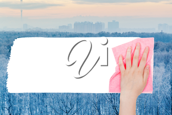 weather concept - hand deletes frozen forest by pink rag from image and white empty copy space are appearing