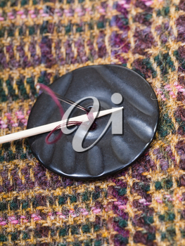 attaching of button to woolen fabric by needle close up