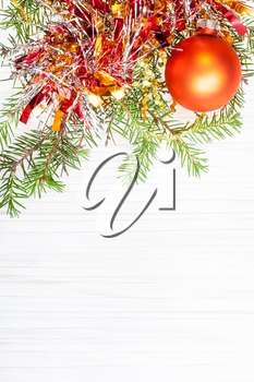 Christmas greeting card - border from one gold Xmas bauble and tree branch on blank paper background