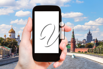 travel concept - hand holds smartphone with cut out screen and Moscow landscape on background
