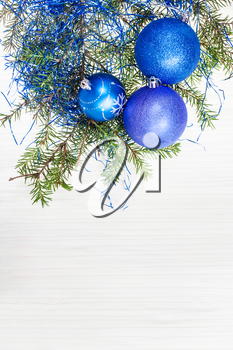 Christmas greeting card - border from blue Xmas decorations and tree branch on blank paper background