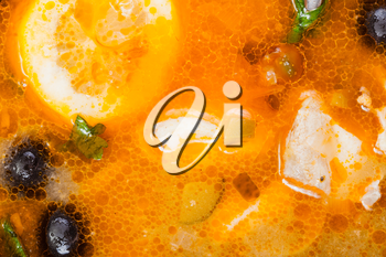 food background - surface of Solyanka russian traditional spicy and sour soup with fish close up