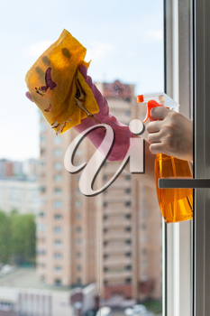 washing home window - cleaner washes window glass with detergent in apartment house