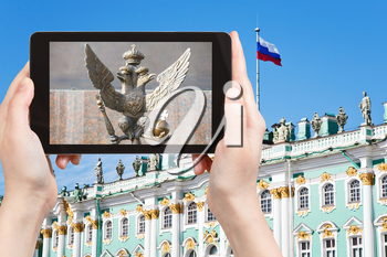 travel concept - tourist photographs Double-headed eagle symbol of Russian Empire near Winter Palace in Saint Petersburg, Russia on tablet pc