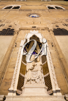 travel to Italy - facade of medieval Orsanmichele church with statue (Madonna of the Rose by sculptor Pietro di Giovanni Tedesco) in Florence city in night