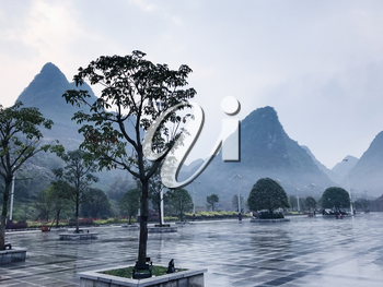 travel to China - wet square and view of karst peaks in Xing Ping town in Yangshuo county in spring rain