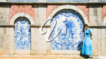 Travel to Algarve Portugal - tourist near outside wall of Estoi Palace with traditional azulejo tile decor in Estoi village. The Palace was built in the late 19th century