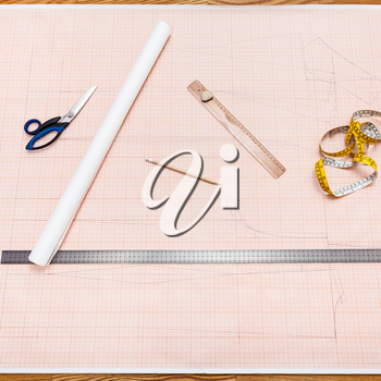 top view of objects to draw a clothing pattern on sheet of graph paper
