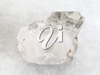 macro shooting of natural mineral rock specimen - rough rock-crystal of quartz gemstone on white marble background