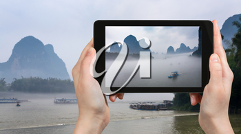travel concept - tourist photographs boats in mist on river near Xingping town in Yangshuo county in spring morning in China on tablet