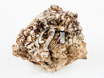macro shooting of natural mineral rock specimen - brown Astrophyllite crystals in rough Natrolite stone on white marble background from Khibiny Mountains, Kola Peninsula, Russia