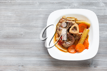 top view of cooked italian dish Ossobuco in white plate on gray wooden board with blank copyspace