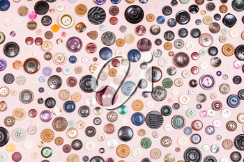 top view of many different buttons on pink background