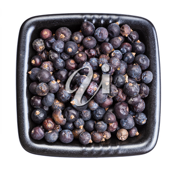 top view of dried juniper berries in black bowl isolated on white background