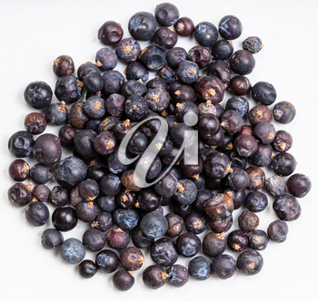 top view of pile of dried juniper berries close up on gray ceramic plate