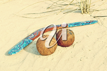 Color Boomerang and two coconuts on sand taken closeup.Toned image.