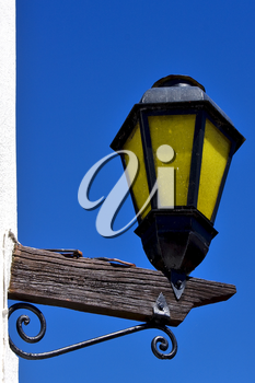 a  street lamp and a white wall  of house in calle de los suspiros in colonia del sacramento  uruguay