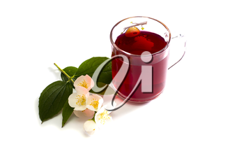 glass of the red tea decorated with a flower branch