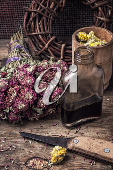 Herbs and glass bulb with decoction of them in rustic style.The image is tinted.