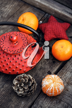 Red cast iron teapot,tangerine,bump and toy on wooden background