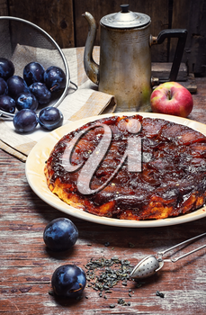 Homemade sweet cake with crop of plums in rustic style