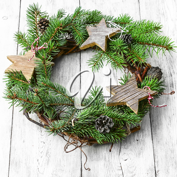 Noel wreath of fir branches decorated with Christmas star toys