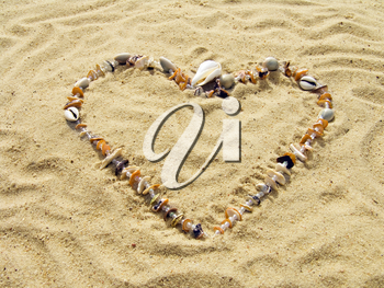 Heart from cockleshells and sea pebbles laid out on sand