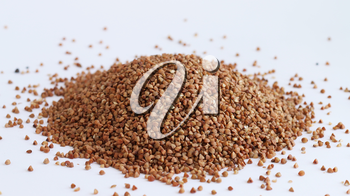 Pile of buckwheat on white background. Agriculture food raw seed. Closeup macro photo