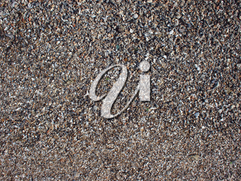 Top view of wet sand and small stones with fragments of shells on the beach closeup. It can be used as a background.