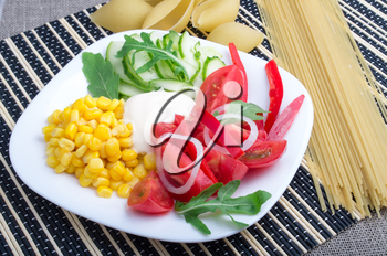 Slices of fresh raw vegetables on a white plate - pepper, tomato, corn, arugula, cucumber, mozzarella cheese on a striped background with pasta and spaghetti