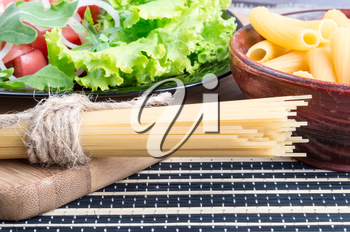 Detail of table with natural food closeup - fresh green salad, pasta in a wooden bowl and a bunch of spaghetti on a wooden board