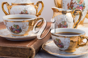 Vintage porcelain coffee cups with hot espresso and retro dishware from the German Bavaria 19th century