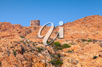 Old Genoese tower on Capo Rosso cliff, Corsica, France. Piana region