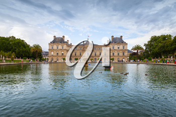Paris, France - August 10, 2014: Luxembourg Palace and reflection in the pond with fountain. Luxembourg Garden in Paris