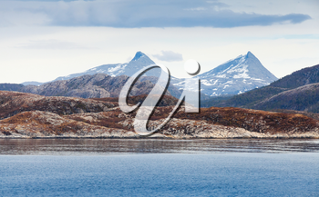 Spring Norwegian landscape with sea coast and mountains with snow