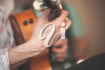 Live music background. Strong hands of an acoustic guitar player, close-up photo with selective focus