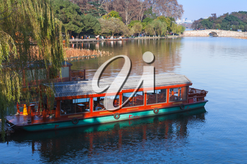 Traditional Chinese red wooden recreational boat stands moored on the West Lake coast. Famous public park in Hangzhou city, China