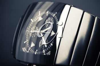Luxury mens chronograph watch made of black high-tech ceramics lays on dark backdrop. Closeup studio photo with tonal filter and selective focus