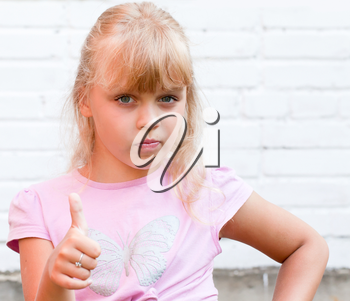 Portrait of a little blond beautiful Russian girl with thumbs up above white brick wall background