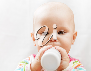 Little brown eyed Caucasian baby with bottle of milk