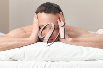 Portrait of Young man in bed with headache