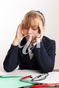 Portrait of blond Caucasian schoolgirl with headache