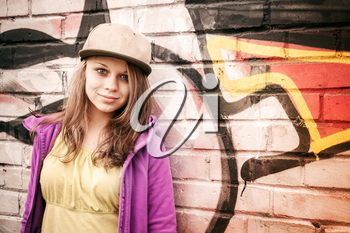 Blond stylish teenage girl stands near urban wall with graffiti, photo with warm retro tonal correction effect, instagram old style filter