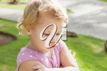 Outdoor closeup portrait, funny Caucasian blond baby girl resentfully pouts