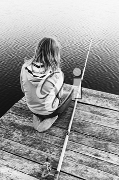 Little blond Caucasian girl sitting on a wooden pier with fishing rod, black and white photo, vertical composition