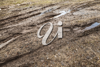 Dirty road with puddles and mud, countryside transportation background