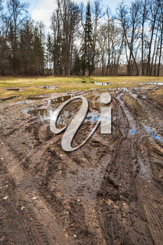 Dirty rural road with puddles and mud in springtime