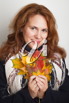 Portrait of beautiful smiling Young Caucasian woman with colorful autumn maple leaves