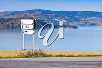 White information road sign stands near rural European highway, Norway