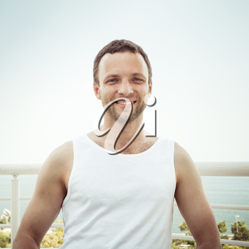 Outdoor summer portrait of Young sporty smiling European man in white shirt, vintage toned square photo